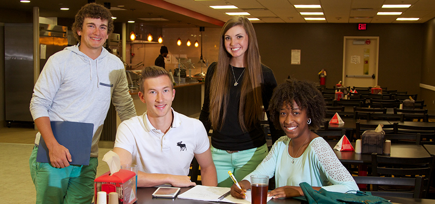 Four students sitting at a table in the dining hall
